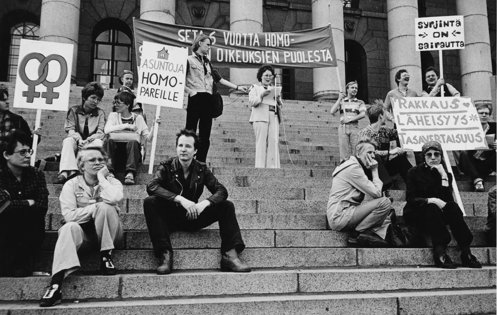 """Demonstranter på riksdagshusets trappor. Skyltarna pryds av dubbla venustecken samt texterna """"Lägenheter för homosexuella par"""", """"Diskriminering är sjukdom"""" och """"Kärlek, intimitet, jämlikhet."""" På en stor banderoll i mitten står """"Seta sex år för homosexuella rättigheter"""", en del av banderolltexten skyms av de människor som står framför den."""