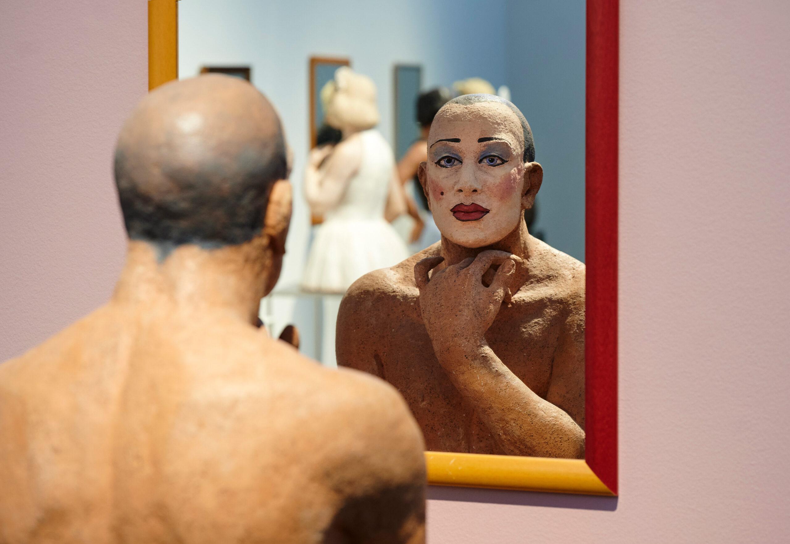 Kuvan keskellä on peili, jonka edessä on veistos. Veistoksen kasvot heijastuvat peilistä, ja kasvot ovat vahvan naamiomaisen meikin peitossa.