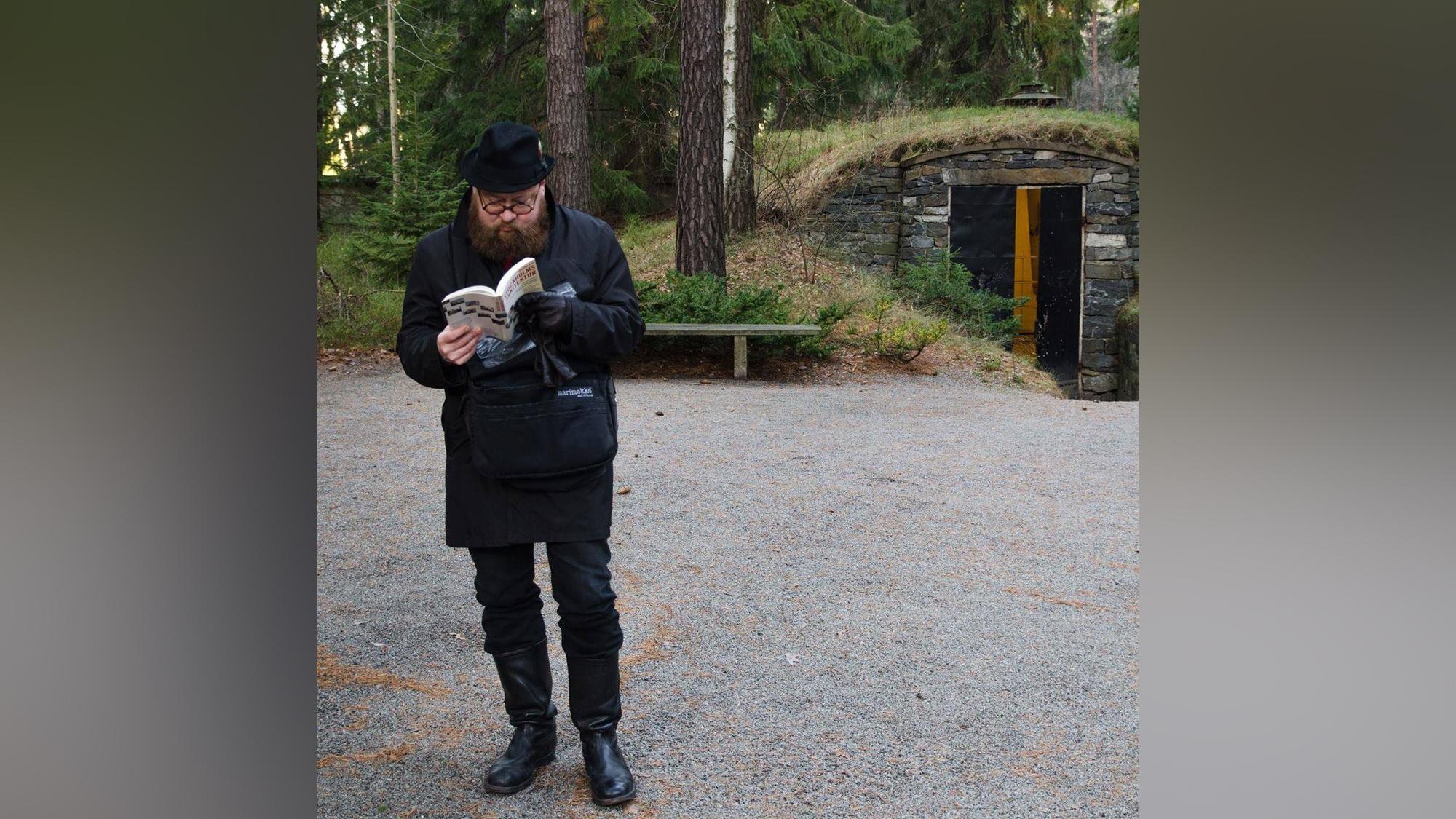 Mustiin pukeutunut parrakas ja silmälasipäinen henkilö seisoo hiekkakentällä ja lukee kirjaa. Taustalla näkyy metsää ja perunakellaria muistuttava rakennus, jonka ovi on auki.
