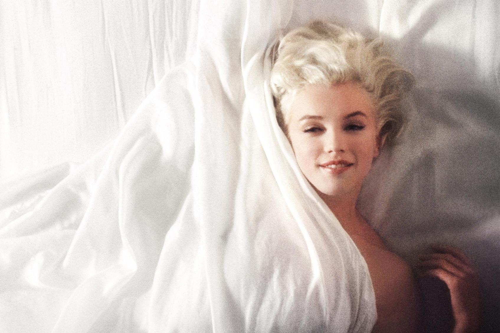 Kuva on otettu suoraan ylhäältä. Marilyn Monroe makaa alasti valkoisten lakanoiden alla pehmeässä sivuvalossa.