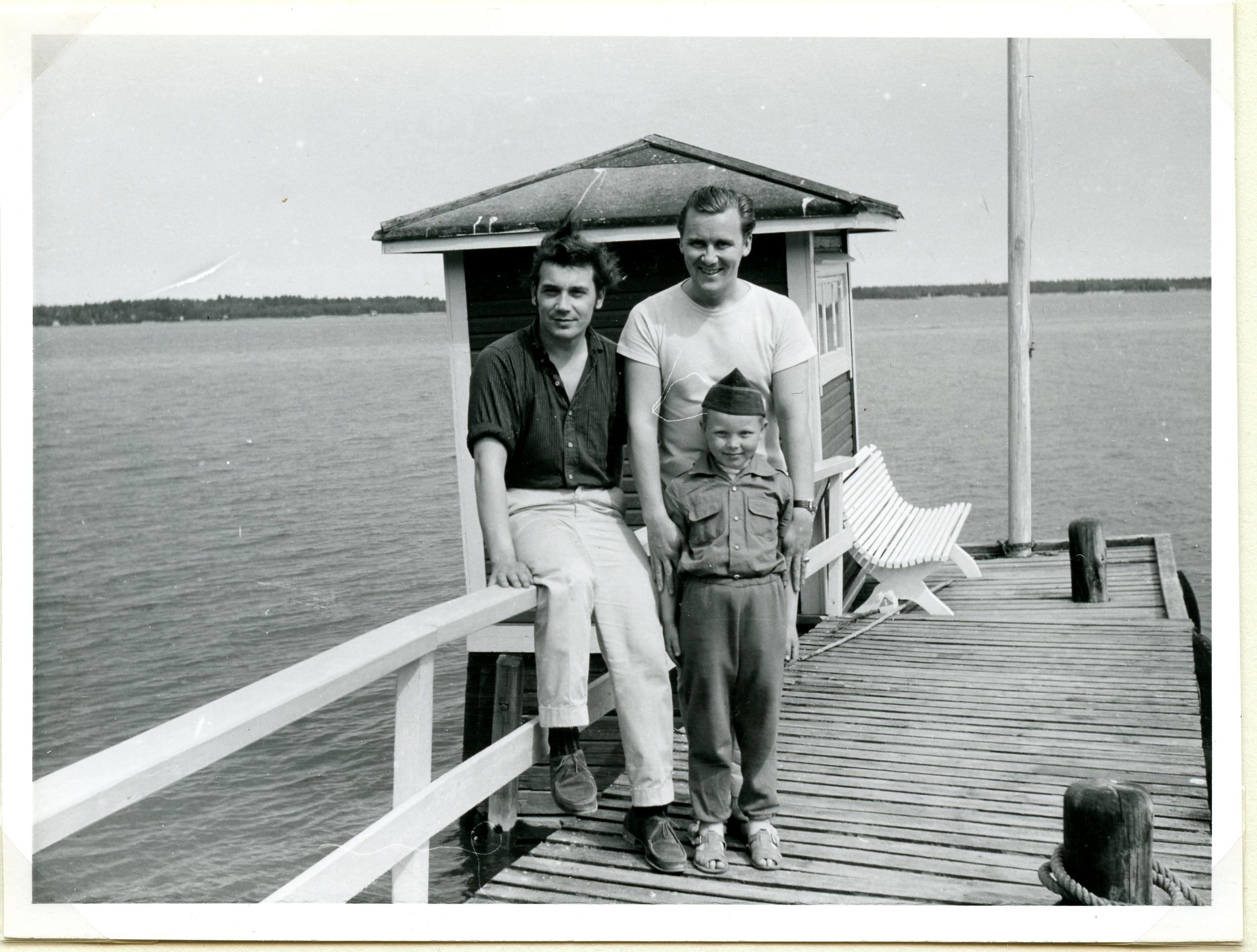 Mustavalkoinen valokuva kahdesta laiturilla seisovasta miehestä. Toisen heistä edessä seisoo lapsi. Kaikki kolme katsovat kameraan ja hymyilevät. Taustalla näkyy uimahuone ja iso vesialue.
