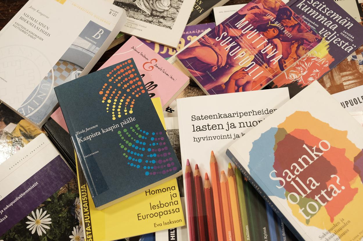 Kirjoja kasassa kuvattuna ylhäältä päin. Päälimmäisissä näkyvissä kansissa kansissa on kirjojen nimet Homona ja lesbona Euroopassa sekä Saanko olla totta.