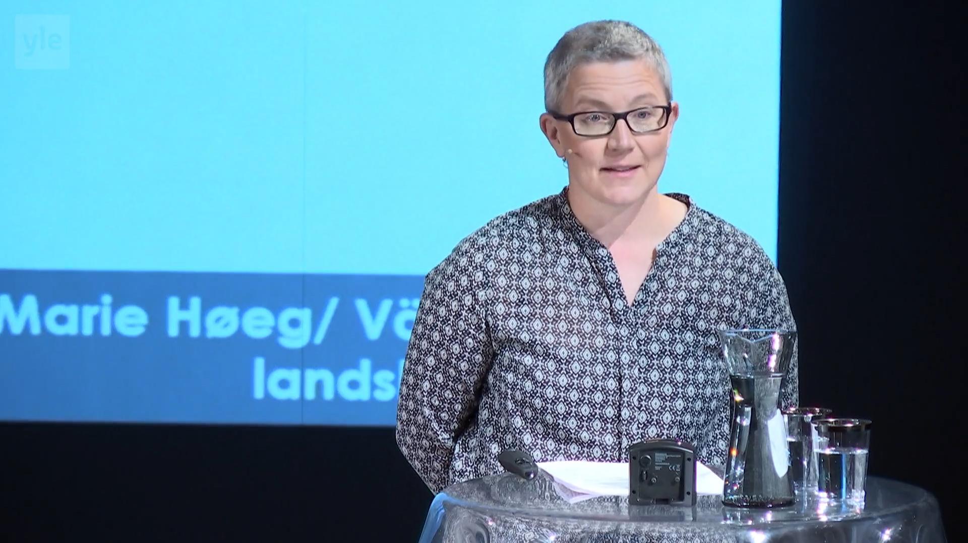 Rita Paqvalén puolikuvassa pitämässä esitelmää.
