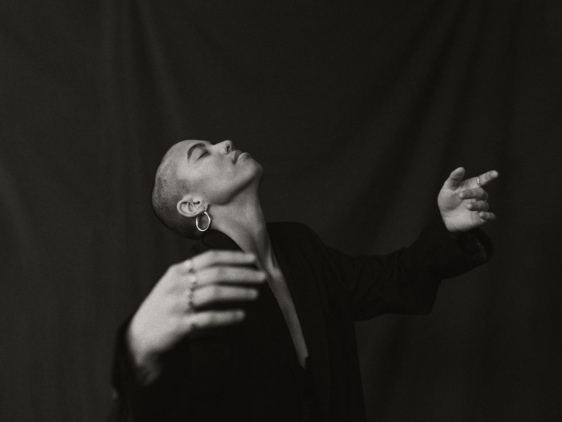 Mustavalkoinen kuva henkilöstä tummalla taustalla. Henkilöllä on silmät kiinni, pää taakse taivutettuna ja kädet rennosti auki avattuna.