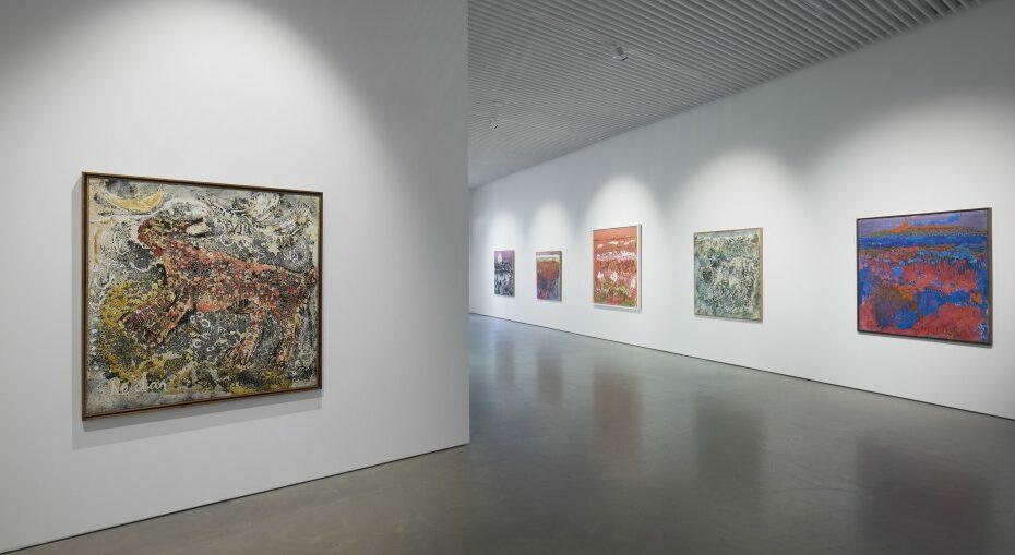 Näkymä Reidar Särestöniemi -näyttelystä. Eri värisiä ekspressiivisiä maalauksia ripustettuna valkoisille seinille.
